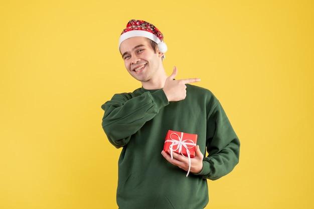 Vue de face jeune homme avec bonnet de noel montrant quelque chose sur fond jaune