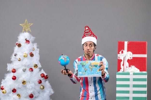 Vue de face jeune homme avec bonnet de noel printemps en spirale à la recherche de cadeaux tenant la carte du monde et le globe
