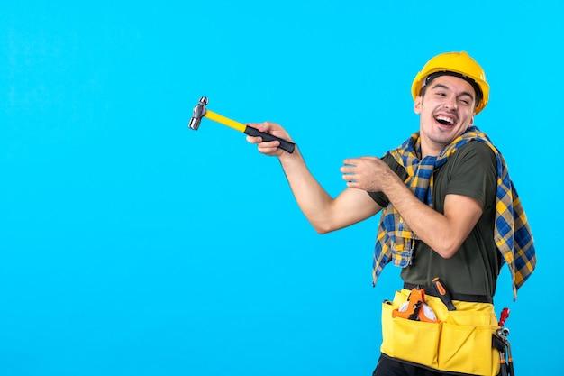 Vue de face jeune homme builder holding hammer riant sur le fond bleu house job télévision construction travailleur architecture constructeur