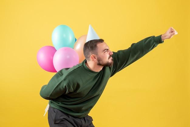 Vue de face jeune homme cachant des ballons colorés derrière son dos sur fond jaune