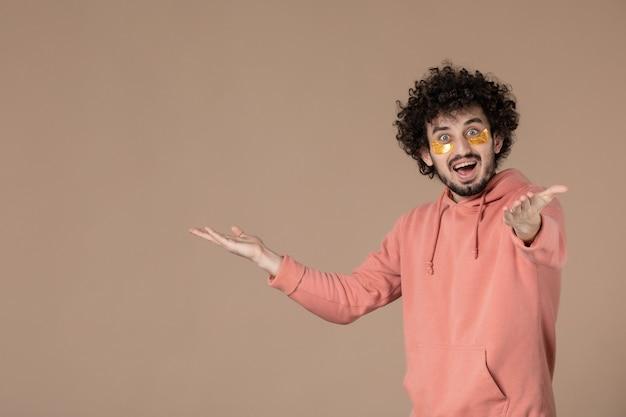Vue de face jeune homme avec des cache-œil sur fond marron beauté spa soins du corps crème massage peau couleur du visage