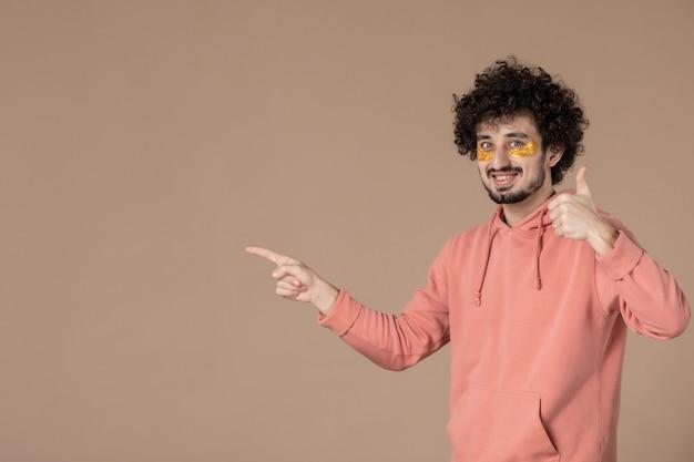 Vue de face jeune homme avec cache-œil sur fond marron beauté spa soins du corps crème massage peau photo du visage