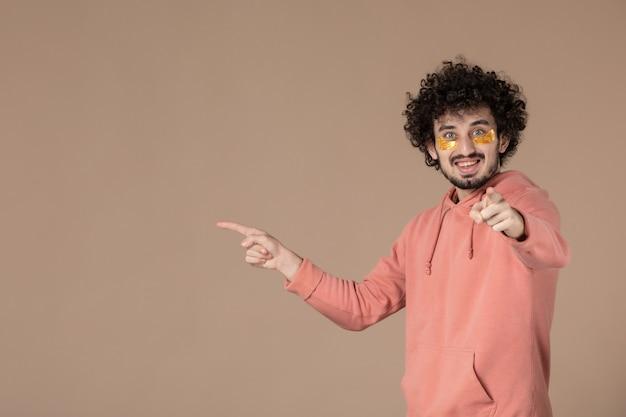 Vue de face jeune homme avec cache-œil sur fond marron beauté spa soins du corps crème de soin massage peau couleurs du visage