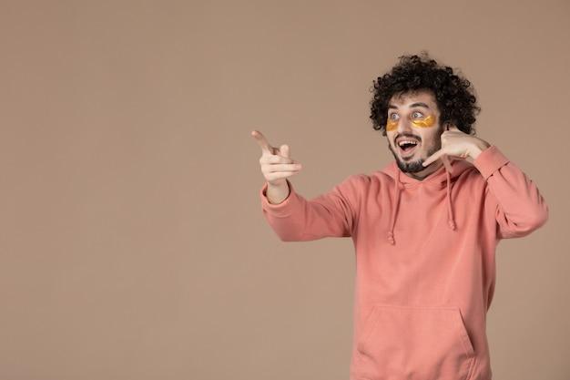 Vue de face jeune homme avec des cache-œil imitant un appel téléphonique sur fond marron crème pour le visage spa beauté soins de la peau