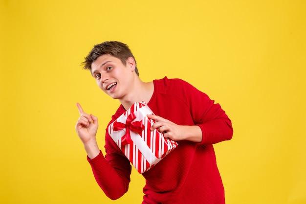 Vue de face jeune homme avec cadeau de noël sur fond jaune