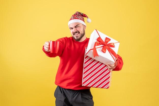 Vue de face jeune homme avec cadeau de noël et tasse de thé sur fond jaune
