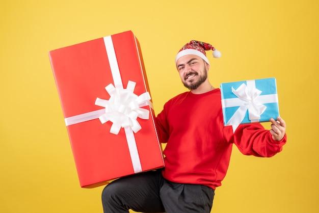 Vue de face jeune homme avec des cadeaux de noël sur fond jaune
