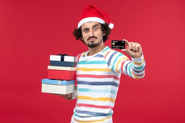 Vue de face jeune homme avec des cadeaux de vacances et carte bancaire sur le bureau rouge nouvel an argent rouge