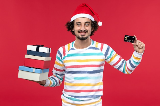 Vue de face jeune homme avec des cadeaux de vacances et carte bancaire sur le mur rouge nouvel an argent rouge