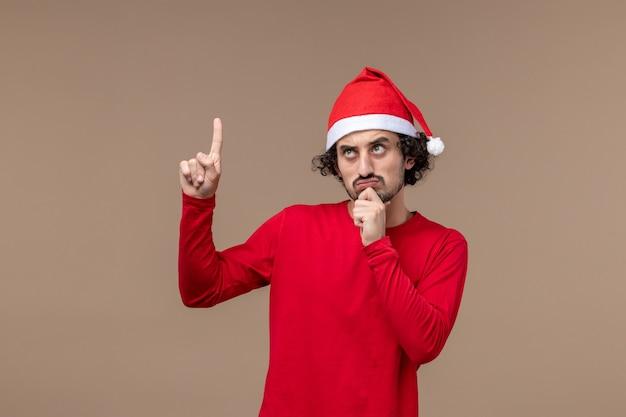Vue de face jeune homme avec cape de noël sur le bureau brun émotion vacances noël