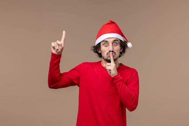 Vue de face jeune homme avec cape de noël rouge sur fond marron vacances émotion noël