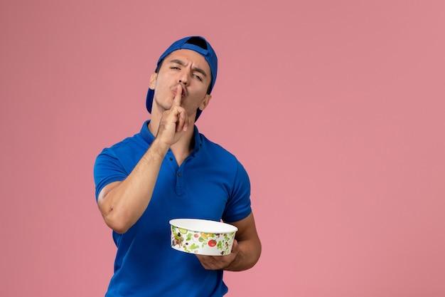 Vue de face jeune homme en cape uniforme bleu tenant un bol de livraison rond demandant d'être calme sur un mur rose clair