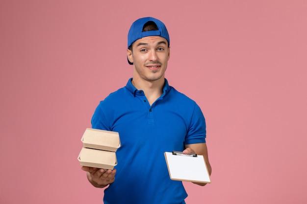 Vue de face jeune homme en cape uniforme bleu tenant peu de colis alimentaires de livraison avec bloc-notes sur mur rose clair