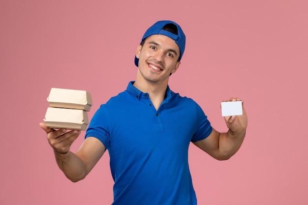 Vue de face jeune homme en cape uniforme bleu tenant peu de colis alimentaires de livraison avec carte sur mur rose clair