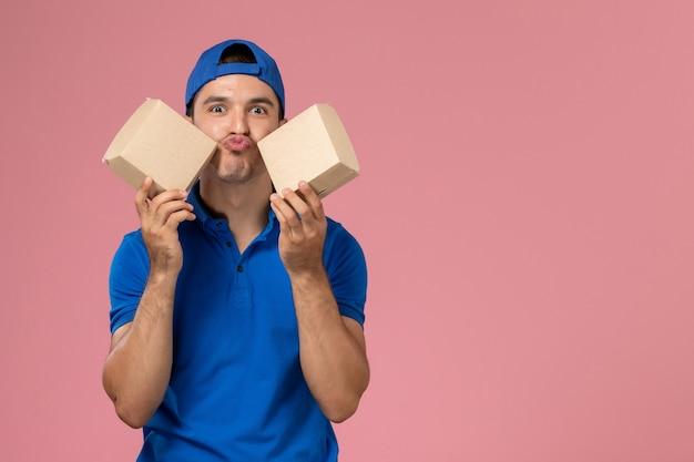 Vue de face jeune homme en cape uniforme bleu tenant peu de colis alimentaires de livraison sur mur rose clair