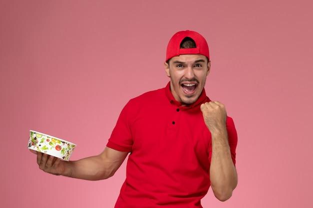 Vue de face jeune homme en cape uniforme rouge tenant le bol de livraison et se réjouissant sur le fond rose clair.