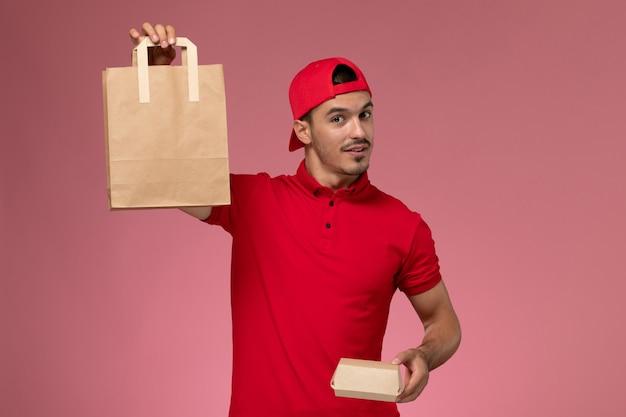 Vue de face jeune homme en cape uniforme rouge tenant deux emballages alimentaires différents sur le fond rose.