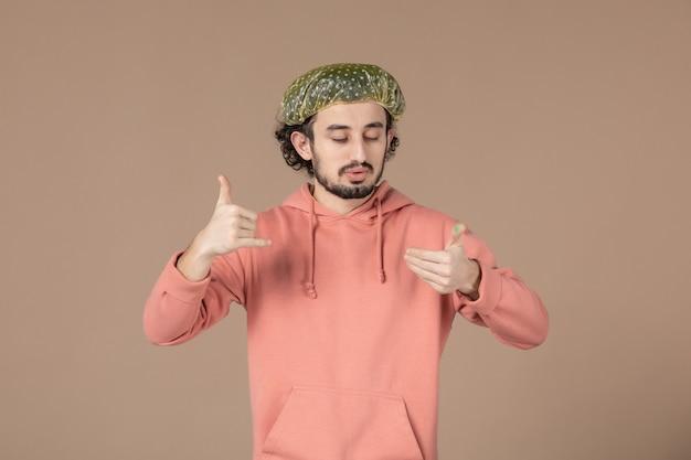 Vue de face jeune homme avec casquette bouffante sur fond marron salon de soins de la peau massage de la peau cheveux spa facial