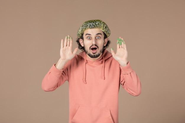 Vue de face jeune homme avec casquette bouffante sur fond marron salon de soins de la peau massage de la peau du visage cheveux thérapie