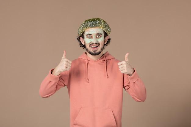 Vue de face jeune homme avec casquette bouffante sur fond marron salon de soins de la peau massage de la peau thérapie cheveux spa
