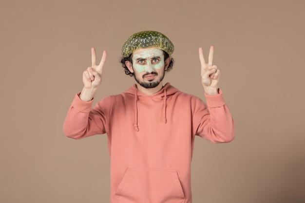Vue de face jeune homme avec casquette bouffante sur fond marron salon thérapie de la peau cheveux massage du visage spa