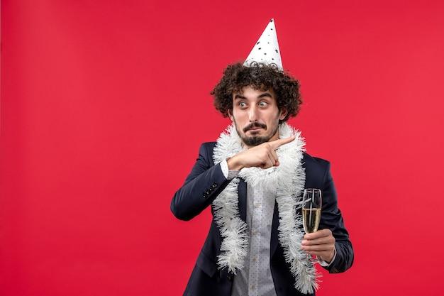 Vue de face jeune homme célébrant une autre année sur le mur rouge partie vacances humaine
