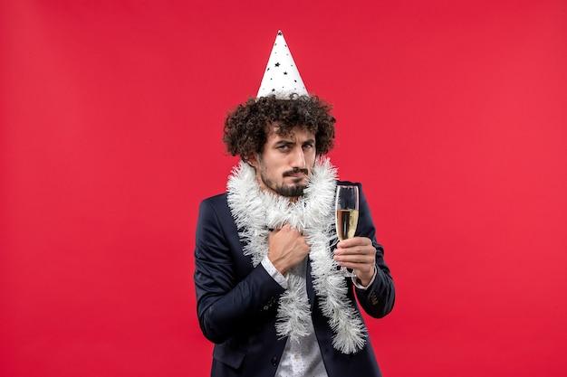 Vue de face jeune homme célébrant une autre année sur le mur rouge partie de vacances humaines