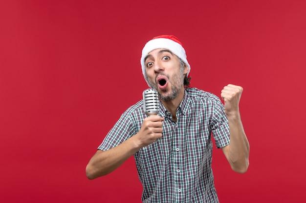 Vue de face jeune homme chantant avec micro sur un bureau rouge