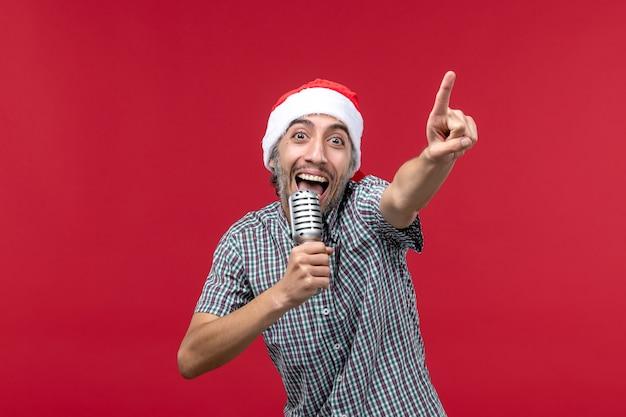 Vue de face jeune homme chantant avec micro sur fond rouge