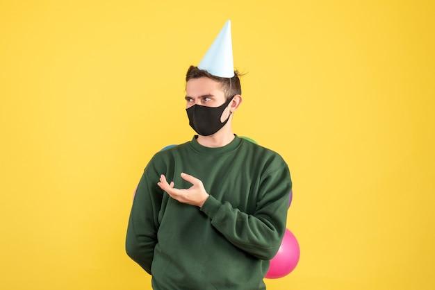 Vue de face jeune homme avec chapeau de fête et ballons colorés debout sur jaune