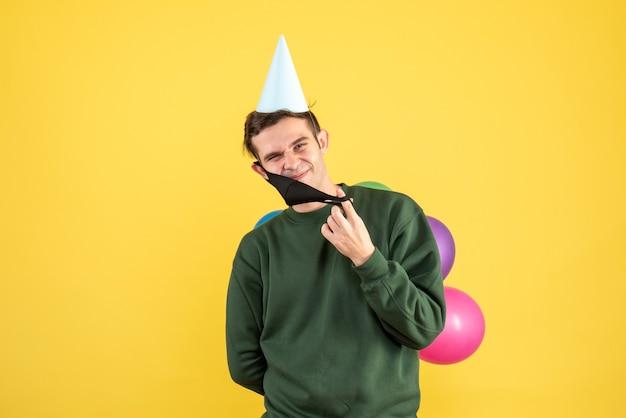 Vue de face jeune homme avec chapeau de fête et ballons colorés décollant son masque sur fond jaune