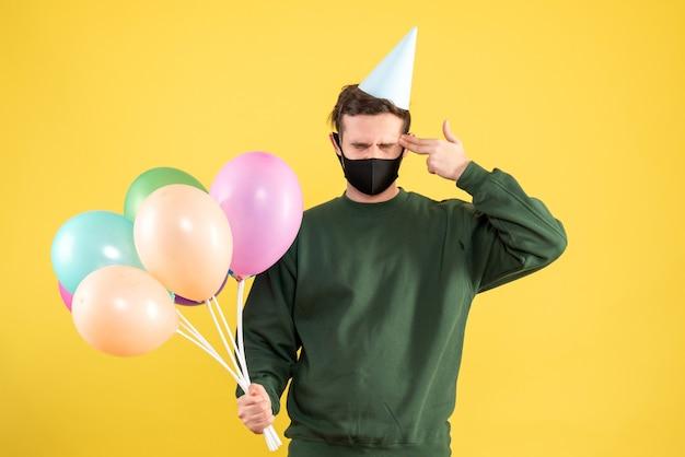 Vue de face jeune homme avec chapeau de fête et ballons colorés mettant le pistolet à doigt à son temple debout sur jaune