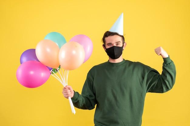 Vue de face jeune homme avec chapeau de fête et ballons colorés montrant des muscles sur jaune