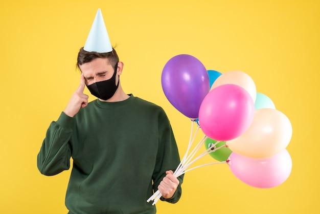 Vue de face jeune homme avec chapeau de fête et ballons colorés tenant sa tête debout sur jaune