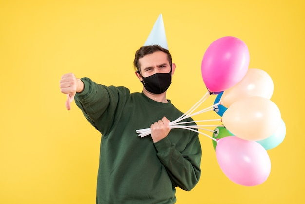Vue de face jeune homme avec chapeau de fête bleu et ballons colorés faisant signe de pouce vers le bas debout sur jaune