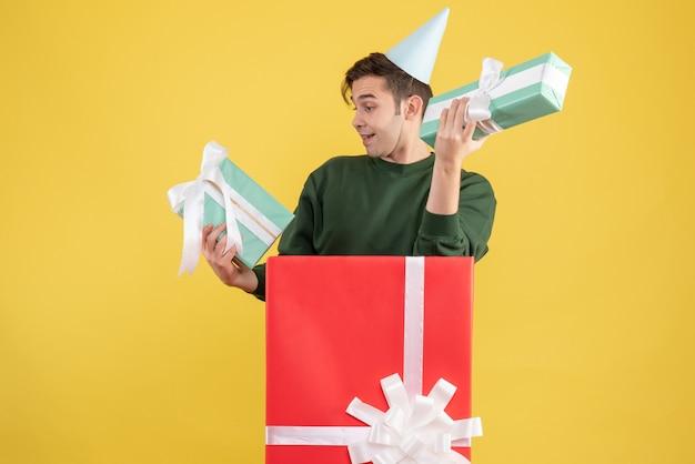 Vue de face jeune homme avec chapeau de fête et cadeaux debout derrière une grande boîte-cadeau sur fond jaune