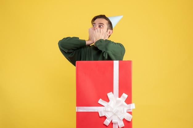 Vue de face jeune homme avec chapeau de fête debout derrière une grande boîte-cadeau sur fond jaune
