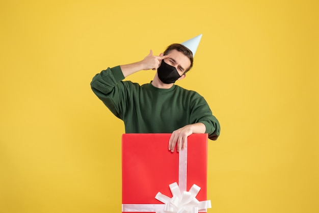 Vue de face jeune homme avec chapeau de fête et masque debout derrière une grande boîte-cadeau sur fond jaune