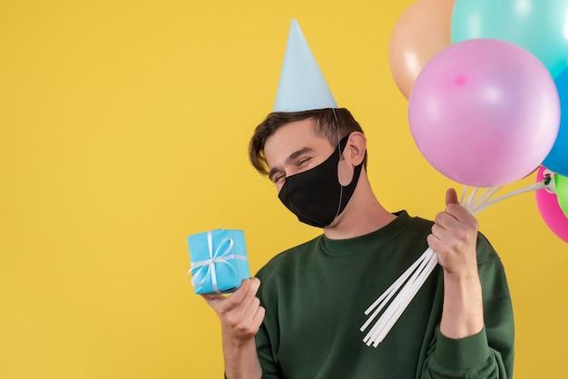 Vue de face jeune homme avec chapeau de fête et masque noir tenant des cadeaux et des ballons sur jaune