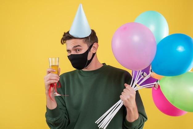 Vue de face jeune homme avec chapeau de fête et masque noir tenant un verre à vin et des ballons sur jaune