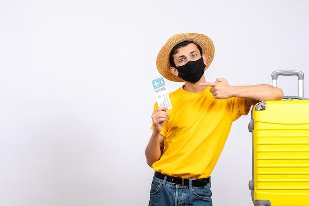 Vue de face jeune homme avec chapeau de paille debout près de valise jaune pointant sur le billet de voyage