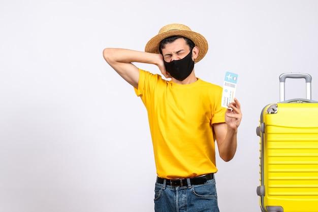 Vue de face jeune homme avec chapeau de paille debout près de valise jaune tenant un billet de voyage et son oreille