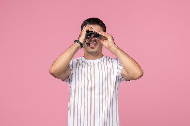 Vue de face jeune homme en chemise blanche à l'aide de jumelles sur fond rose