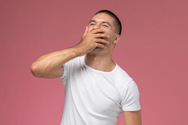 Vue de face jeune homme en chemise blanche riant fortement sur fond rose