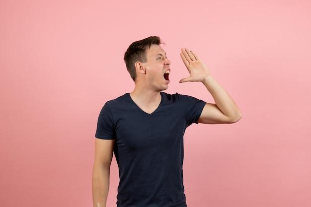 Vue de face jeune homme en chemise bleu foncé criant sur fond rose