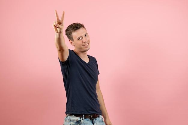 Vue de face jeune homme en chemise bleu foncé sur fond rose clair