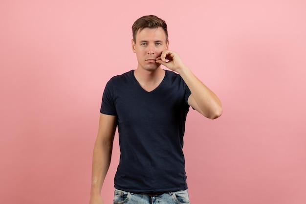 Vue de face jeune homme en chemise bleu foncé sur fond rose