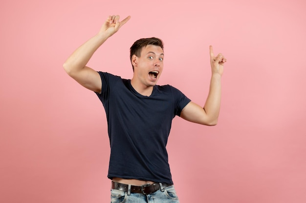 Vue de face jeune homme en chemise bleu foncé posant sur fond rose