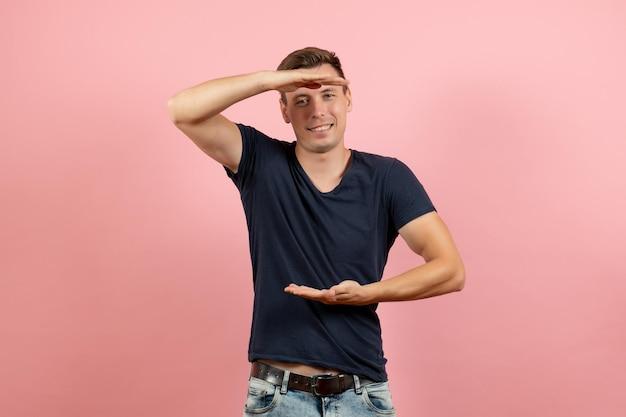 Vue de face jeune homme en chemise bleu foncé posant avec le sourire sur fond rose