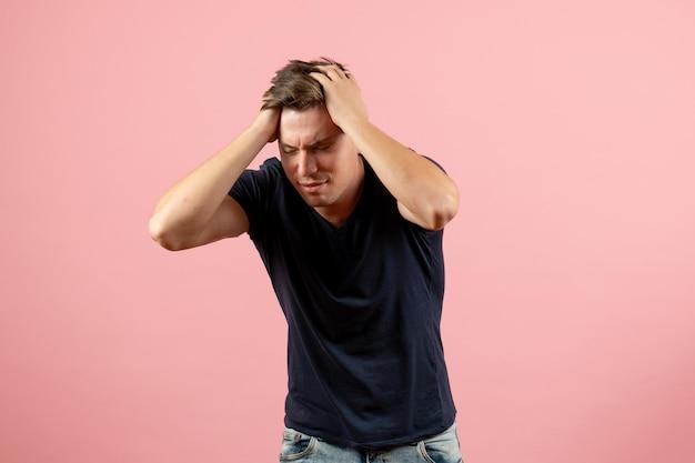 Vue de face jeune homme en chemise bleu foncé posant avec un visage stressé sur fond rose